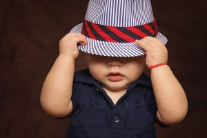 divertida foto de un bebe tapándose la cara con un sombrero, para ilustrar la página de noticias de bebé