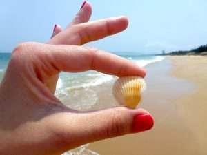manos mostrando uñas pintadas en la playa