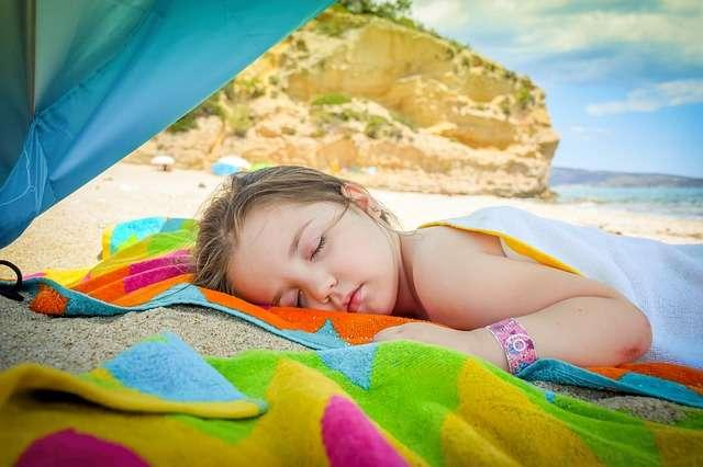 niño duerme siesta en la playa verano