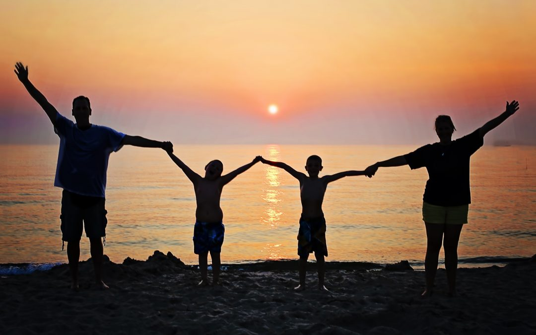 imagen de una familia dados de la mano en una puesta de sol