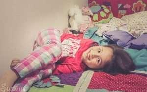 niña en cama sonriendo despertar dormir