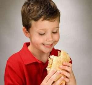 niño tomando un bocadillo merienda comida comer