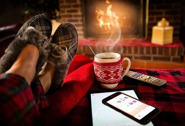 persona en salon con mando de la television junto a movil y taza de cafe hogar chimenea