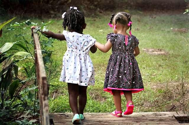 dos niñas de la mano de espaldas infancia solidaridad