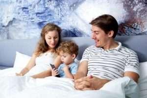 niño con móvil en la cama de los padres pantallas