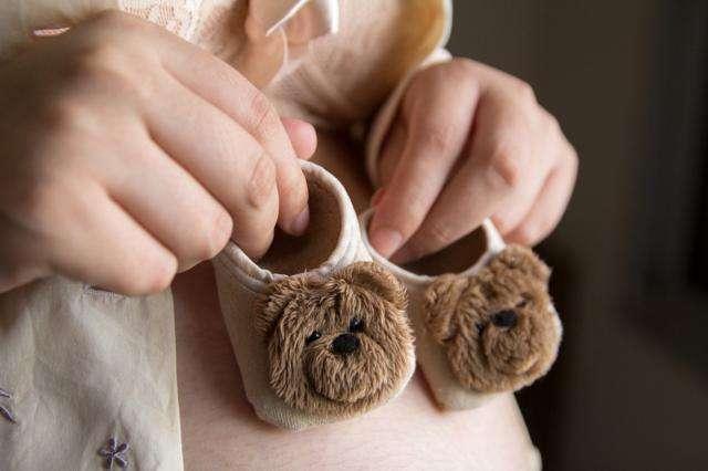tripa de embarazada con patucos de bebé