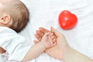 madre da mano a bebé para hablar de volver a trabajar después de baja maternal preparar al bebé y también de cortar las uñas al bebé