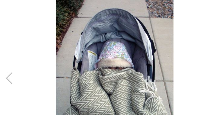 bebé abrigado en cochecito frio