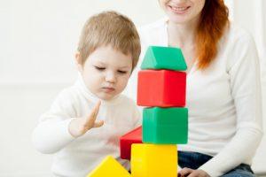 bebé niño jugando con cubos con una chica joven para hablar de consejos elegir cuidadora