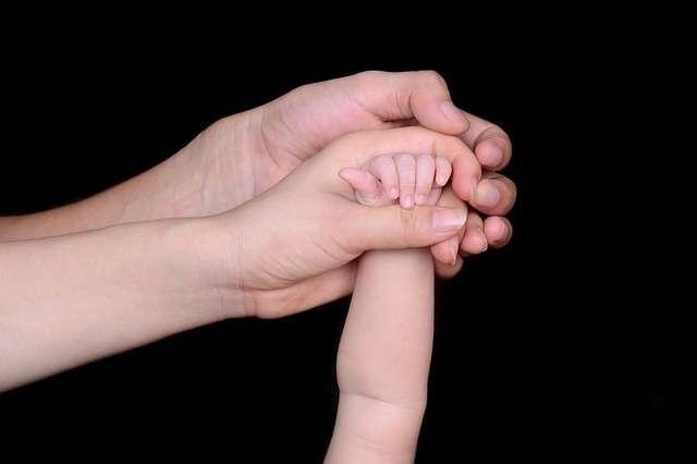 dos manos adultas y una de bebé unidas