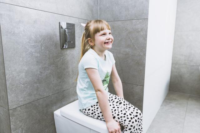 imagen de una niña sonriente sentada sobre un Wc cerrado para hablar de no tirar toallitas húmedas al WC