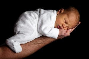 bebé boca abajo apoyando tripa en brazo de su padre recién nacido gases