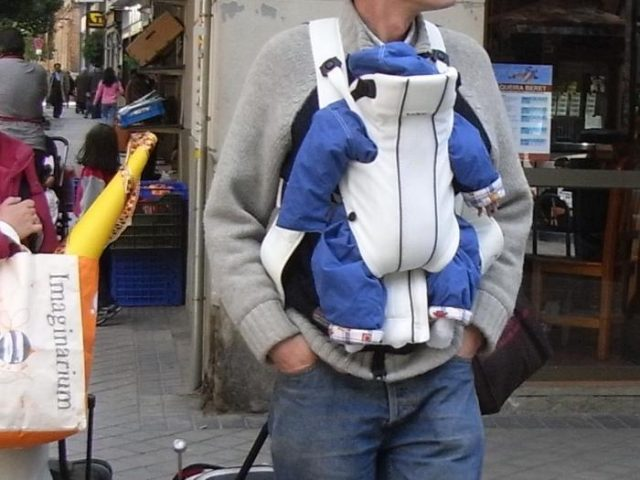 padre llevando a su bebé en una mochila portabebés