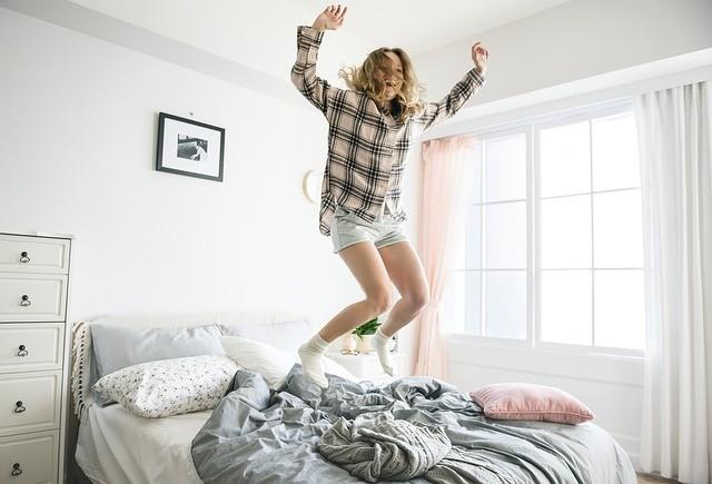 adolescente feliz joven saltando en la cama alegria